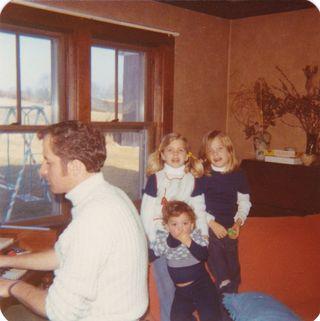 Dad playing organ with we three at farm